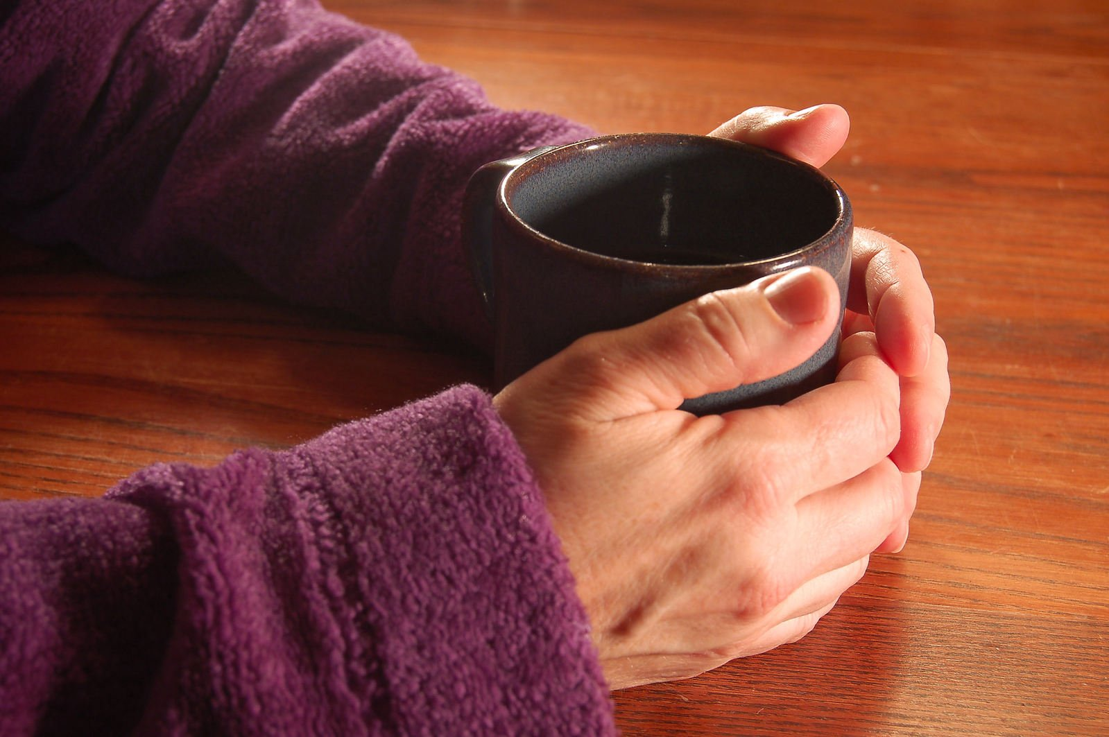 Hands holding a mug of tea, or maybe coffee, could even be hot chocolate!
