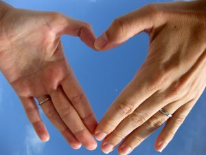 Two hands holding and forming a heart