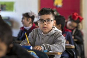 Child sitting at school desk with pencil in his hand