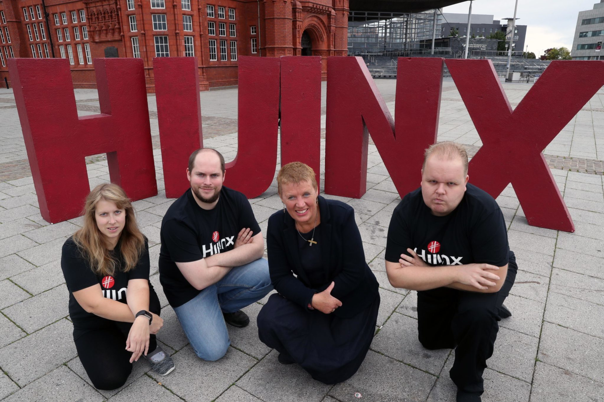 Actors from Hijinx Theatre kneeling infront of large red letters that spell out Hijinx