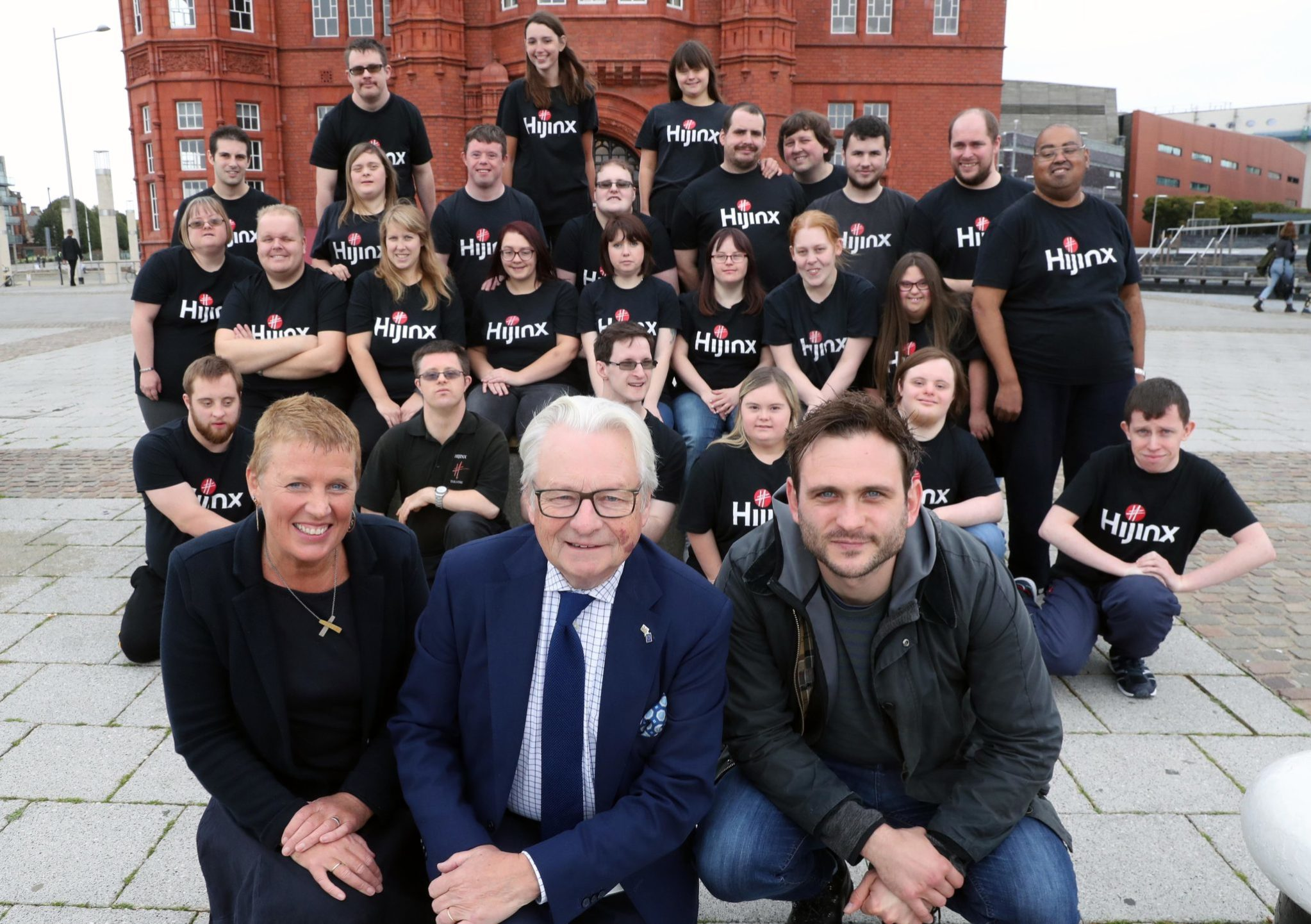 A group of actors from Hijinx Theatre and Lord Dafydd-Elis-Thomas in front of Cardiff's Pierhead Building