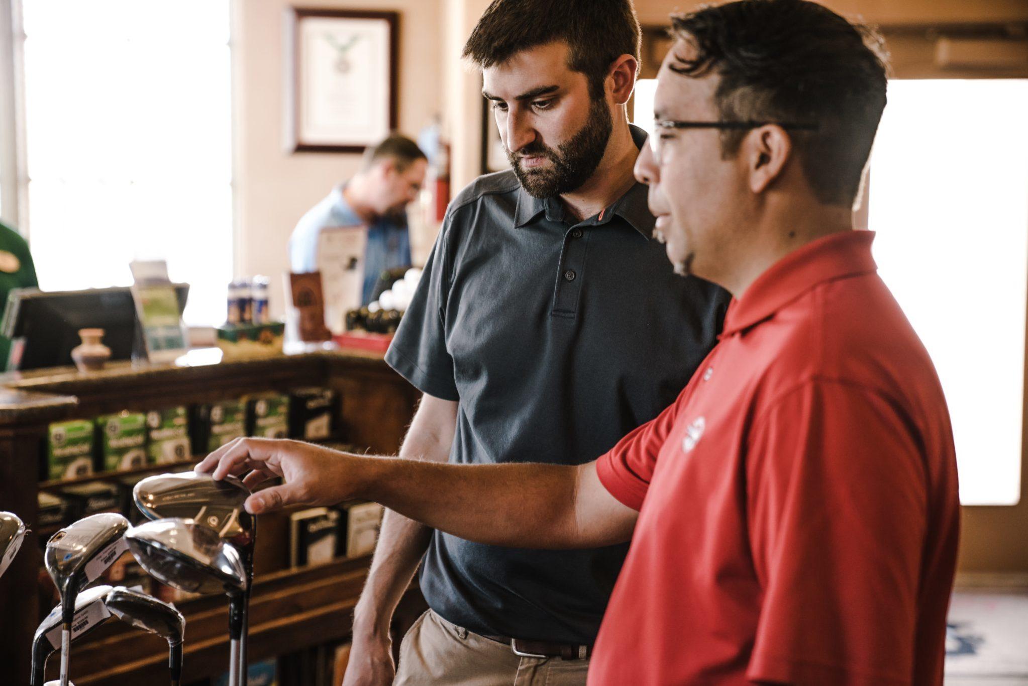Two men choosing golf clubs