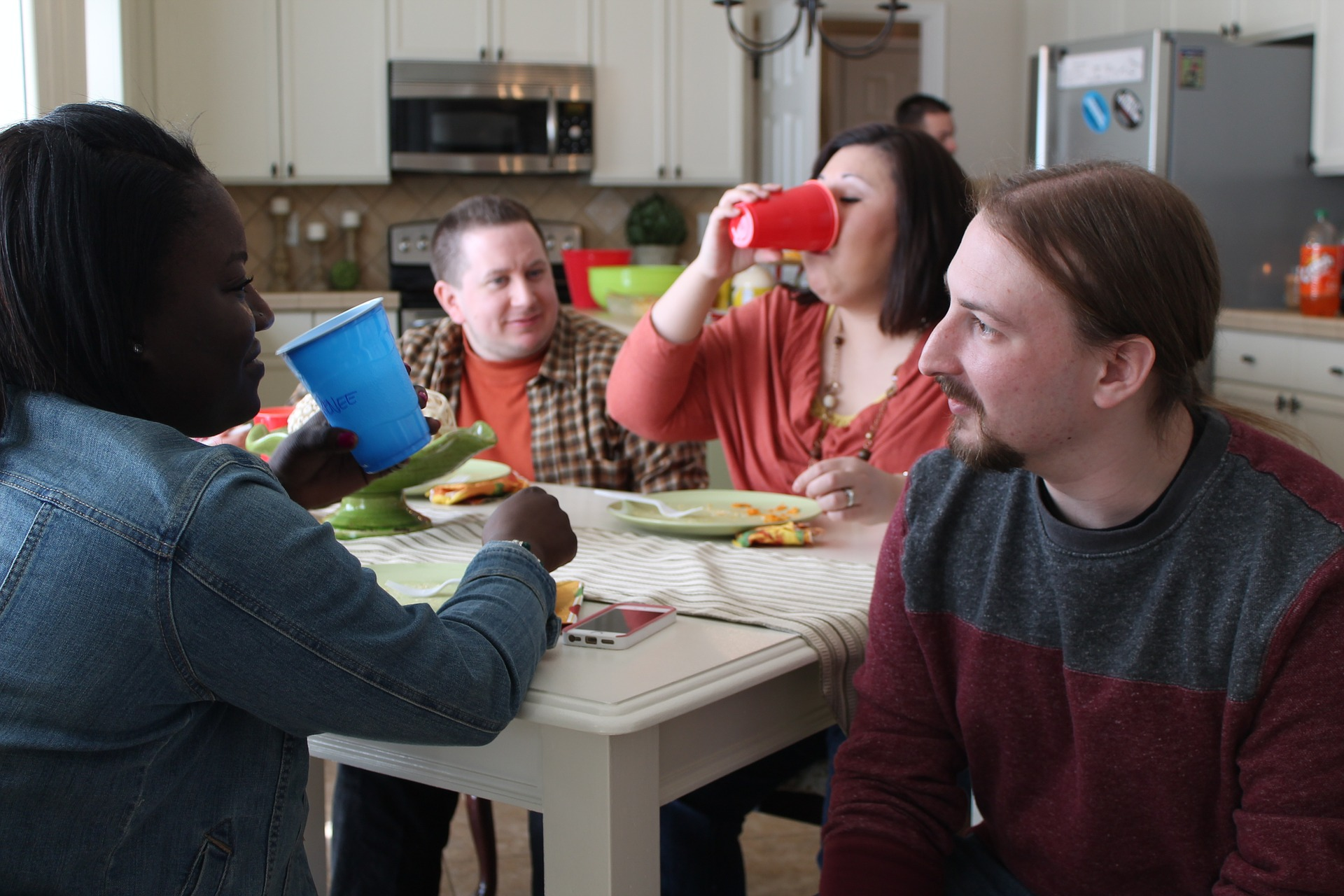 Groups of people around kitchen table, eating and drinking