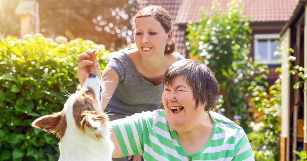 Two women petting a dog.