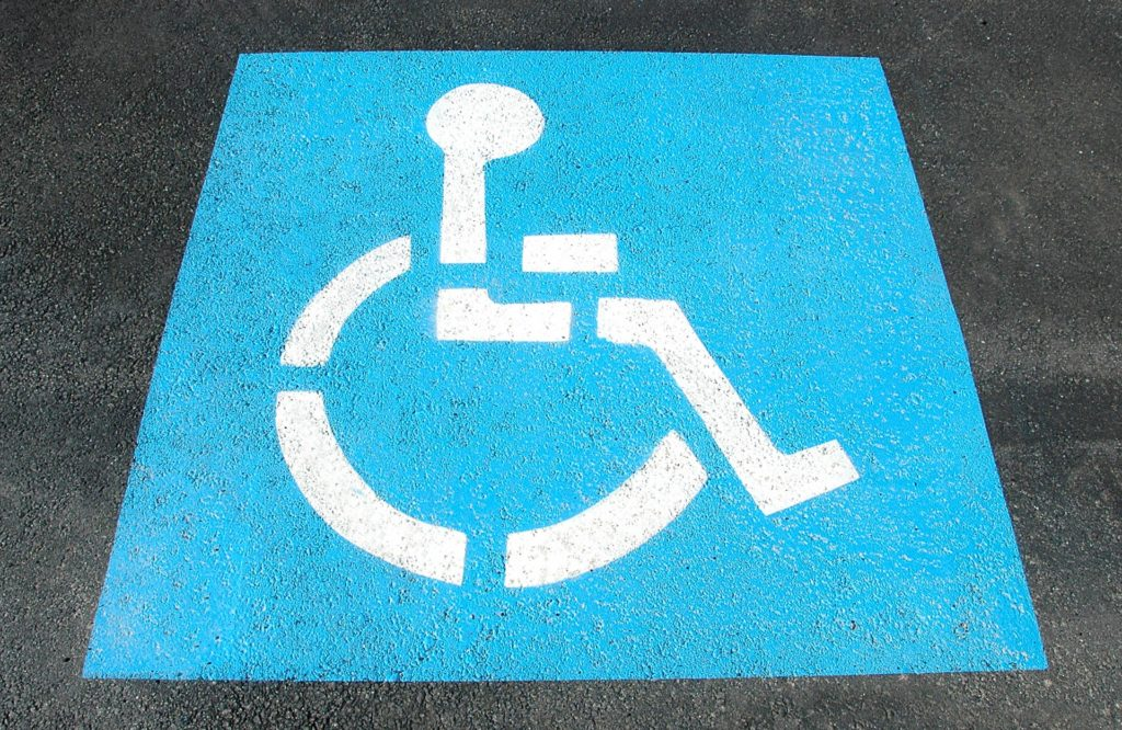 Disabled parking space sign painted on tarmac