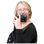 A smiling young woman holding a camera