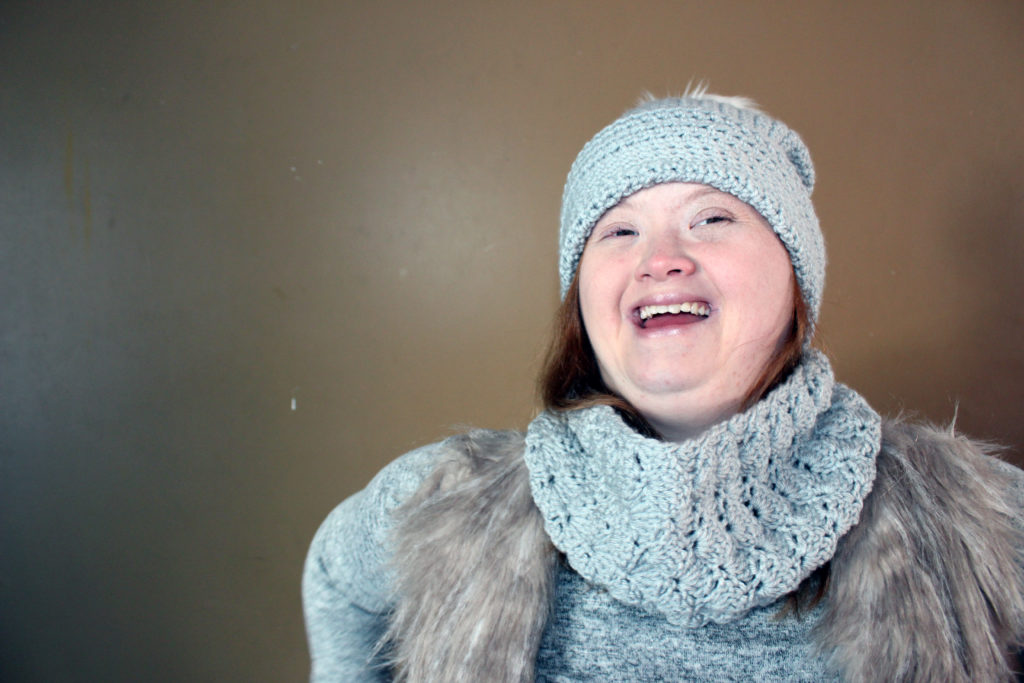 A woman laughing, wearing hat and scarf. She looks confident.