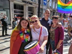 A group of Gig Buddies during the Pride Cymru parade. They are smiling and are wearing lgbt rainbows and have an lgbt rainbow flag