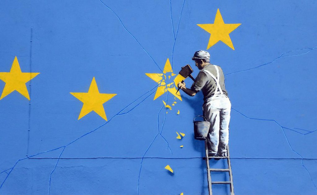 Man in overalls on a ladder removing one of the yellow stars from a gigantic EU flag. Mural is by Banksy