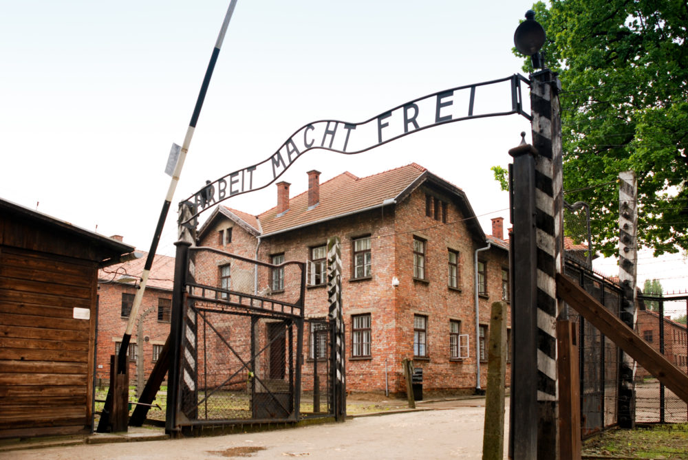 entrance to Auschwitz 1 - barrier is raised next to an iron sign over the entrance that reads in English Work Sets You Free. Behind the barrier are rows of large red bricked buildings