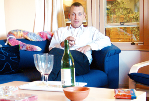 A man sits on a sofa, there is a bottle of wine on the coffee table