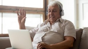 An older man is sitting on a sofa using a tablet to have a video chat