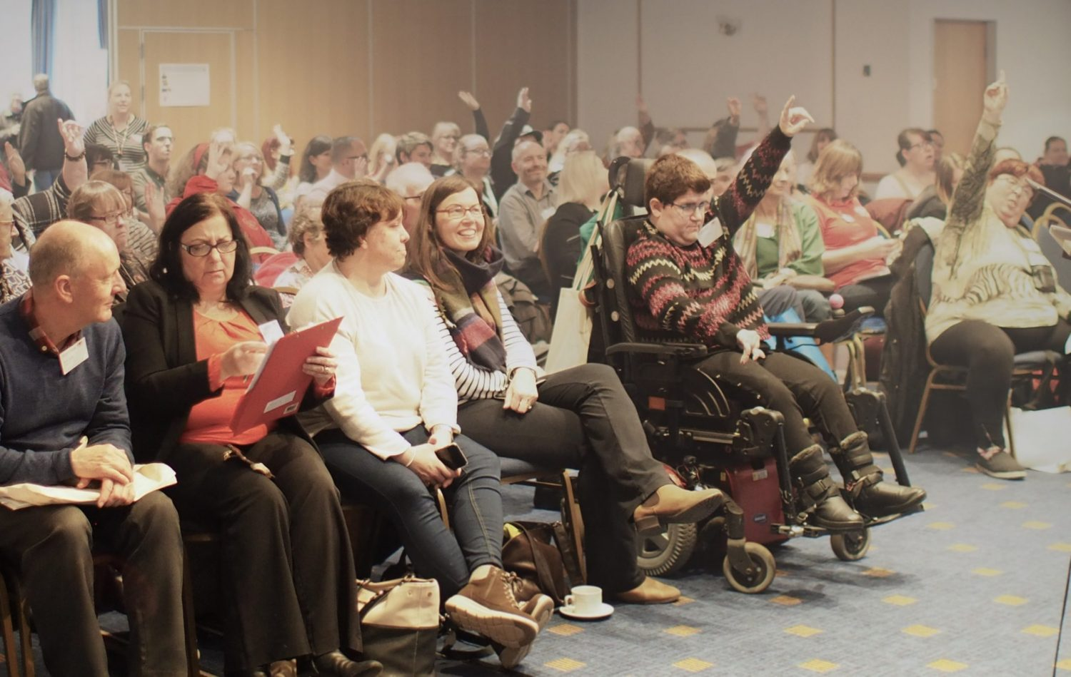 Audience at a Learning Disability Wales conference, some are raising their hands to ask a question