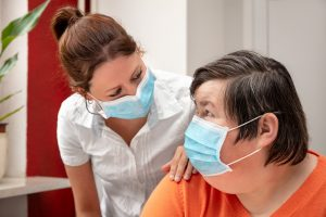 Woman with a learning disability wearing a mask talking to a support worker