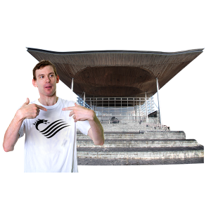 Young man standing in front of the Senedd building with his thumbs up