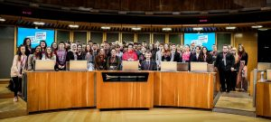 A large group of young people standing together in the Senedd chamber