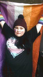 Taylor waving a Lesbian Pride flag and wearing a transgender heart t-shirt